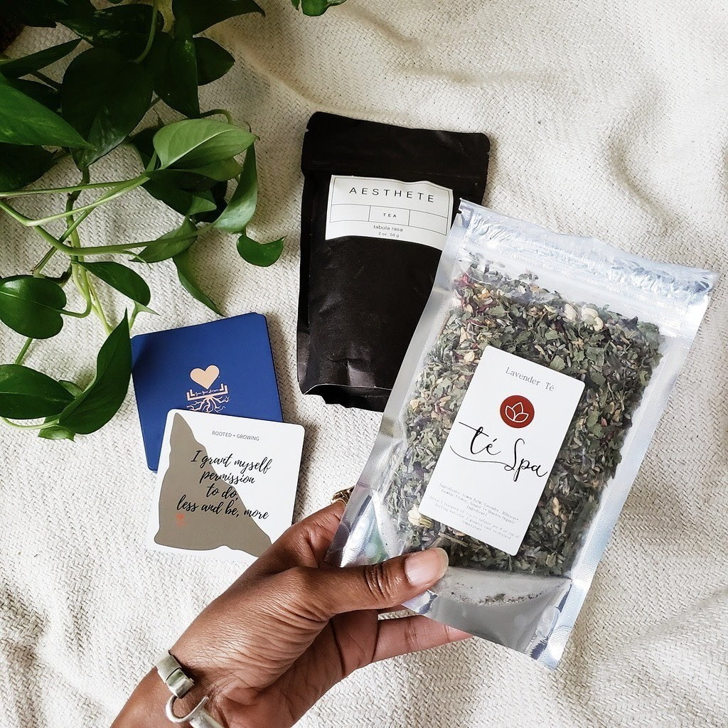 a person holding a bag of loose-leaf tea with other teas in the background