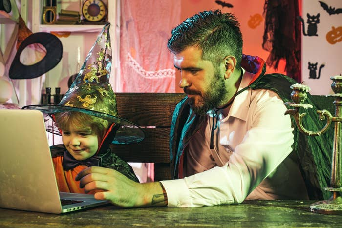 A father and son wear Halloween costumes and search their computer for a movie to watch.