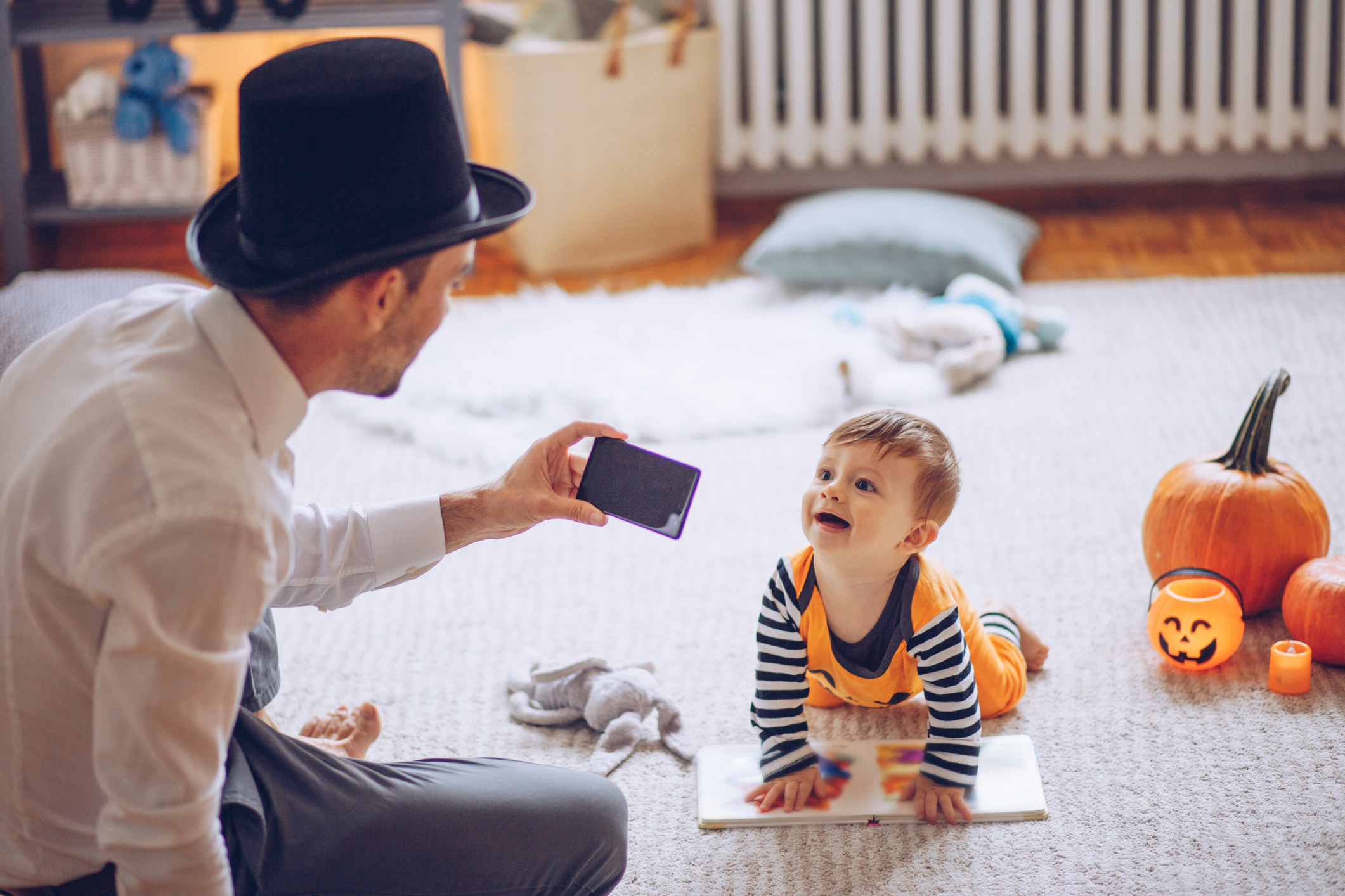A father taking a picture of his baby for Halloween.