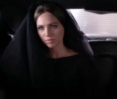 Sara Harvey sitting in the back of a limo dressed as the Black Widow.