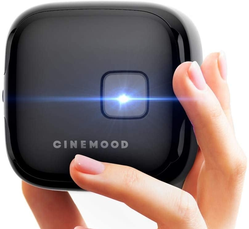 hand holding small black cube-shaped projector