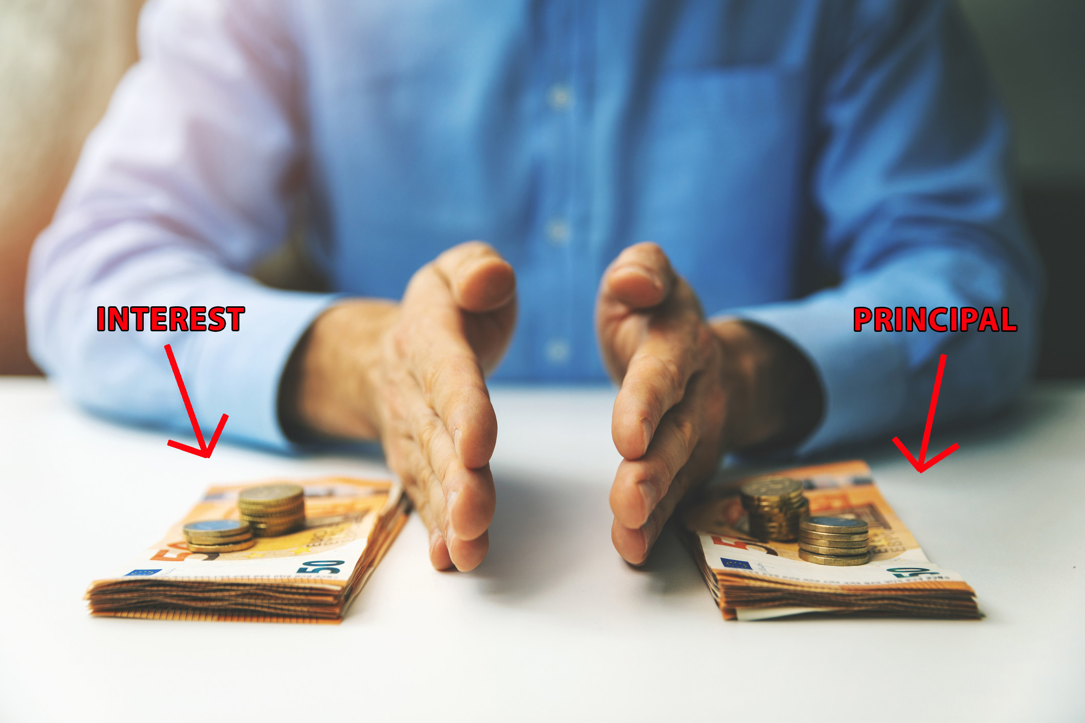 "A man's hands cut between two equal piles of money with arrows reading, respectively, ""interest"" and ""principal"""