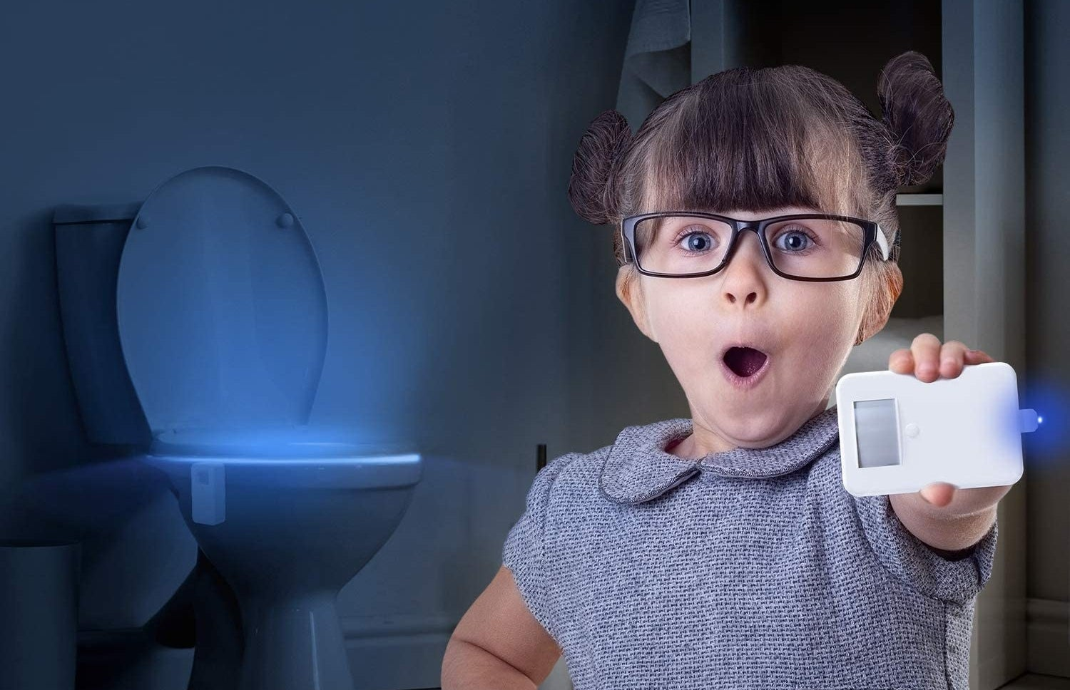 Child model holding toilet light in their hand as blue light glows from toilet