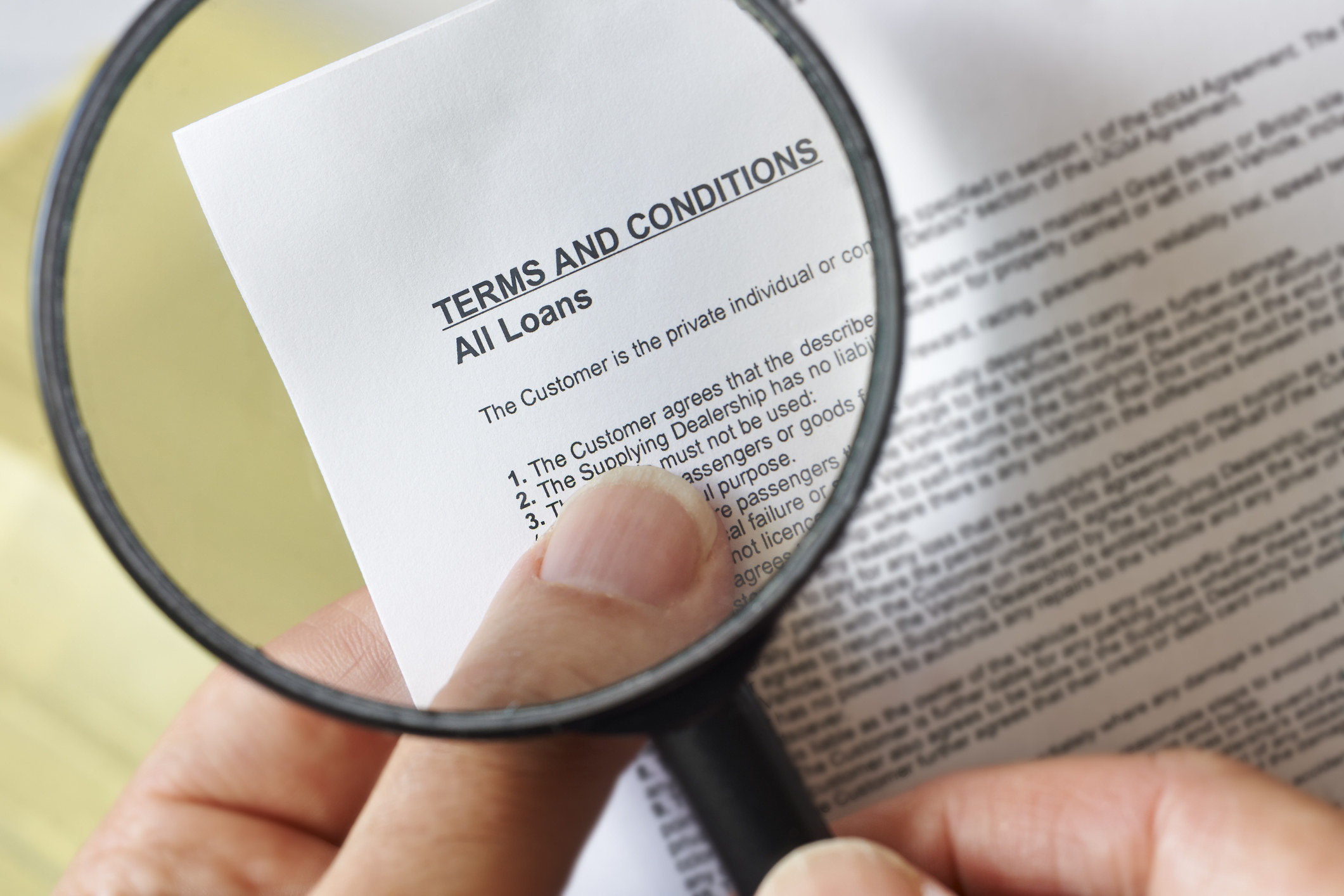 "A magnifying glass reflects a contract reading ""terms and conditions, all loans'"