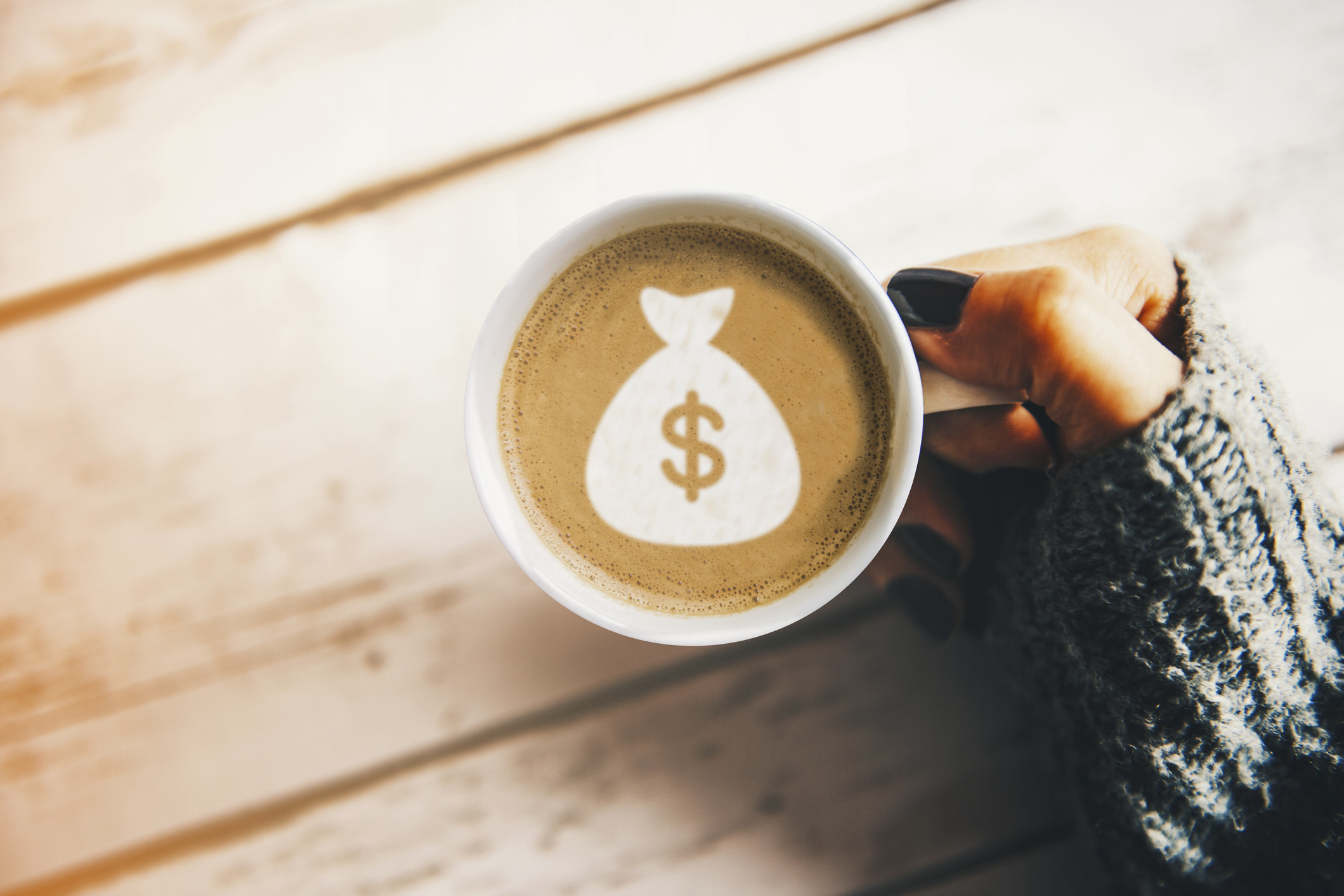 A hand holds a cup of coffee with a foam design of a money bag
