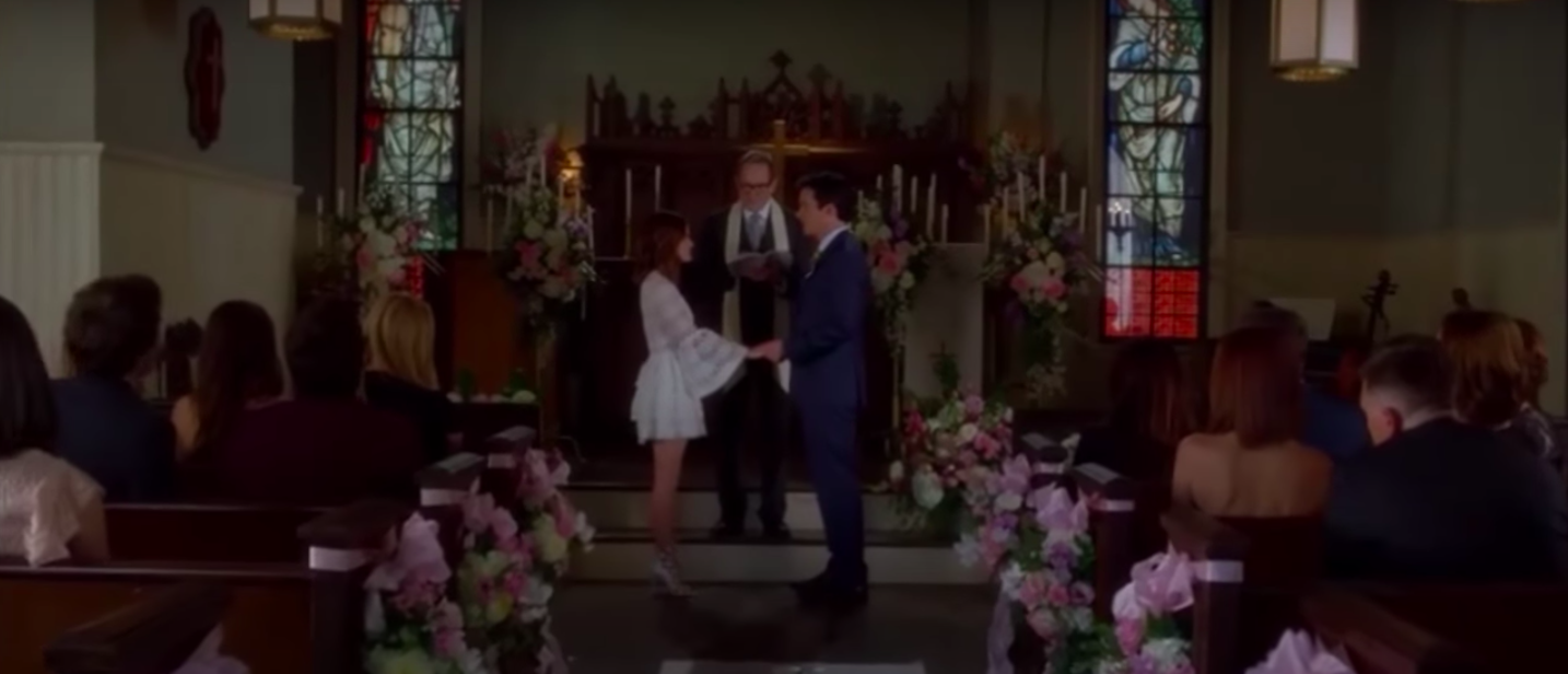 Aria and Ezra at the alter on their wedding day.