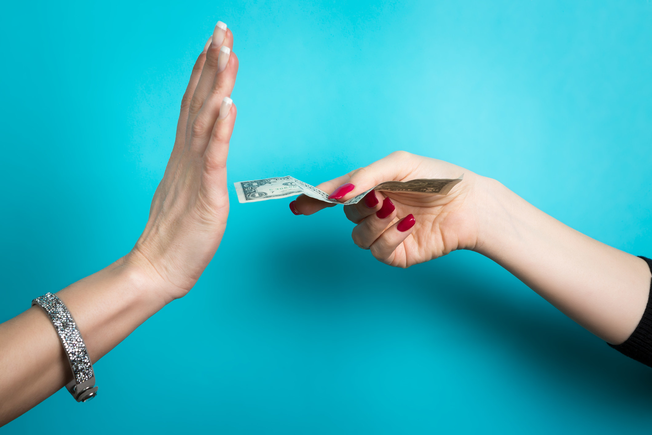 """A hand holds out a bill while another holds up a palm in a """"stop"""" gesture"""
