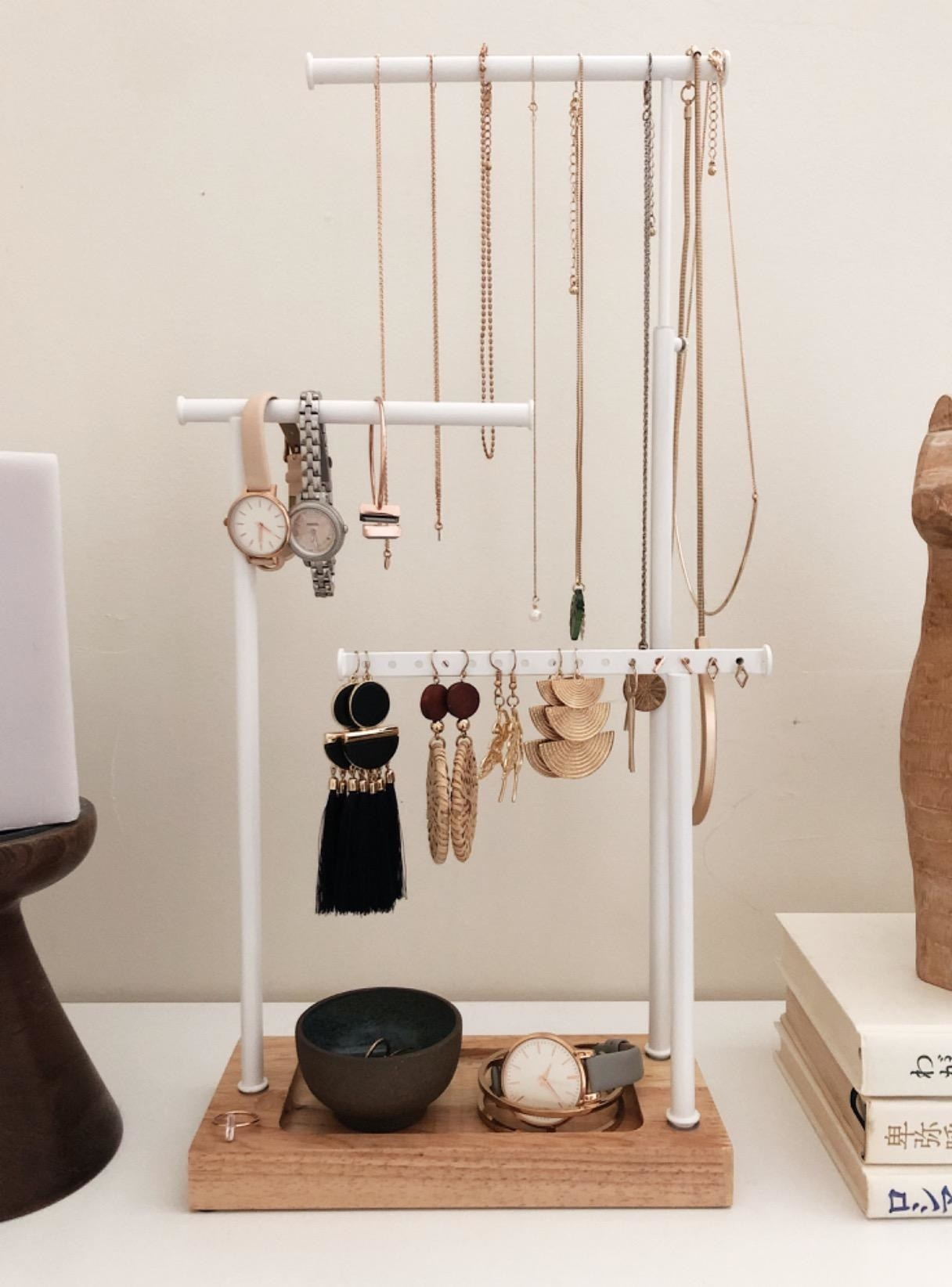 Reviewer pic of the three-tier jewelry stand in white with wood base and jewelry all over it