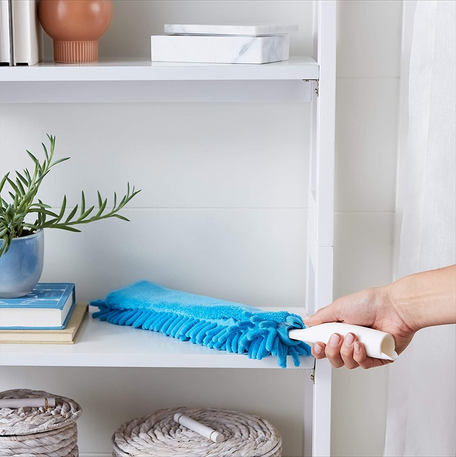 A duster cleans off a shelf