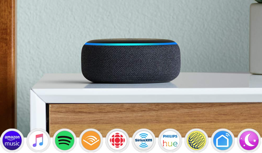 A Echo dot sitting on a bedside table