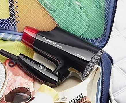 The compact hair dryer folded and placed inside an open suitcase