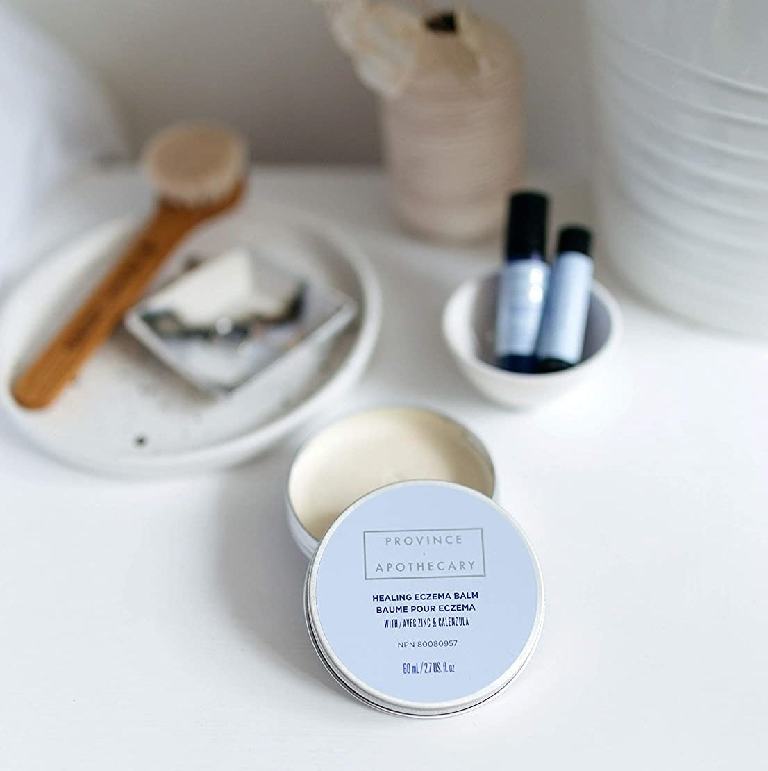 An open tin of the skin balm on a neatly arranged vanity