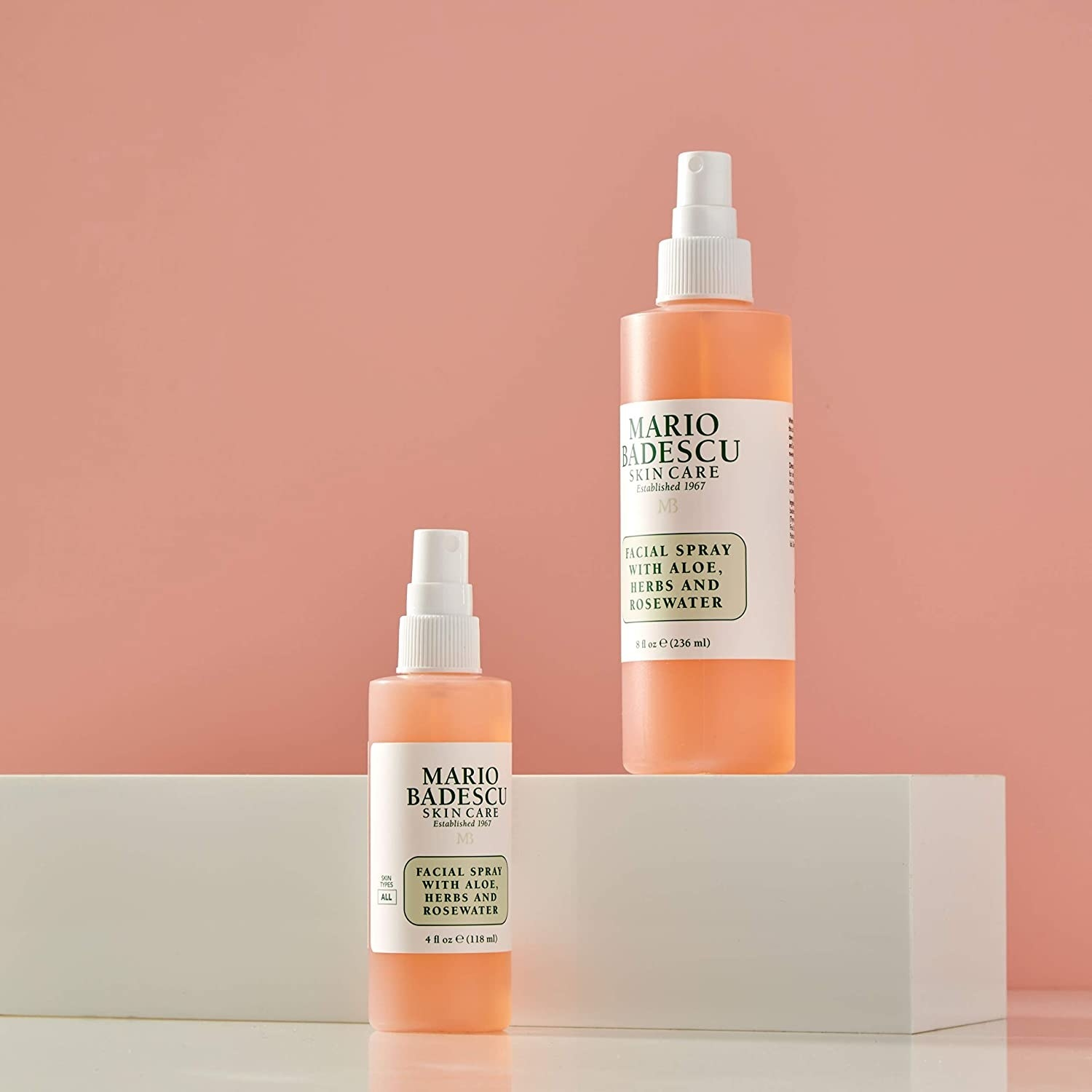 Two bottles of the facial spray on a ledge against a simple backdrop
