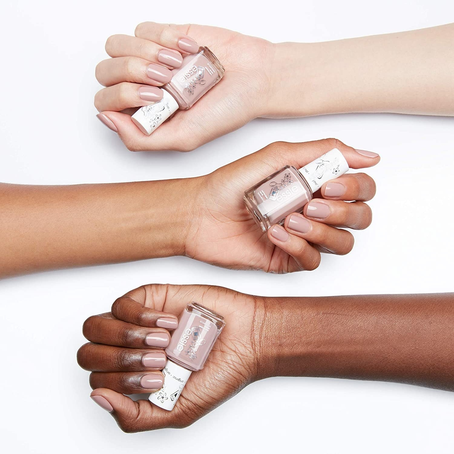 A trio of hands in varying shades all holding the nail polish