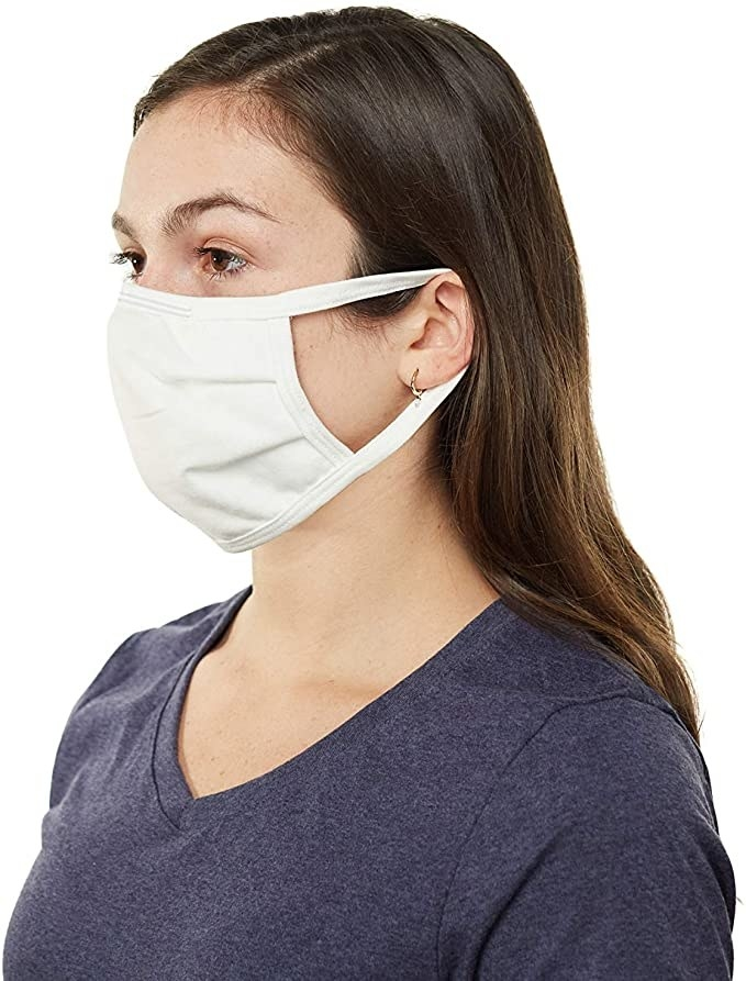 A person wears a face mask with elastics around their ears