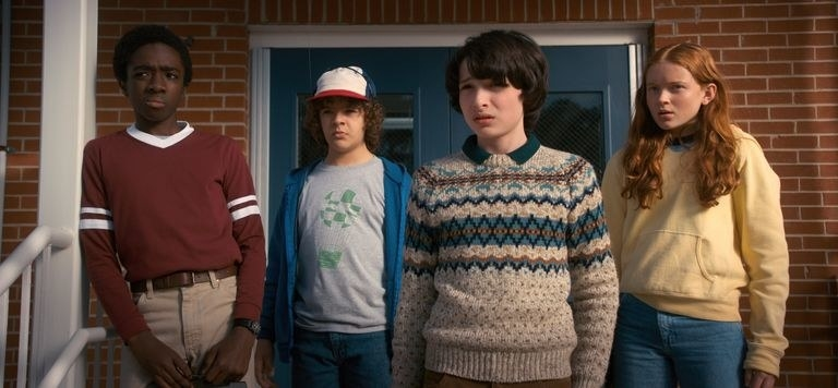 Lucas, Dustin, Mike and Max stand in front of a brick building looking confused