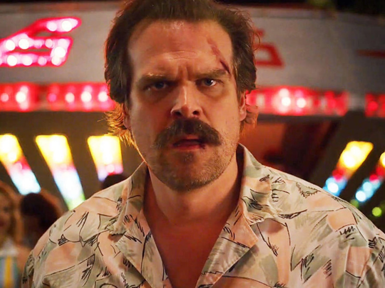 Jim Hopper, frowning, with a bloody lip and a wound on his temple