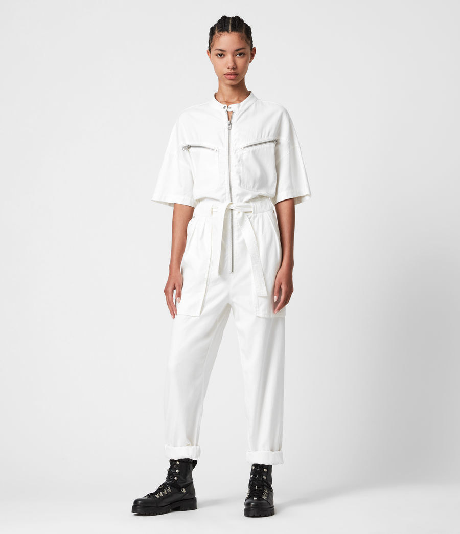 the jumpsuit in white with a loose tie front and zippers across the chest pockets