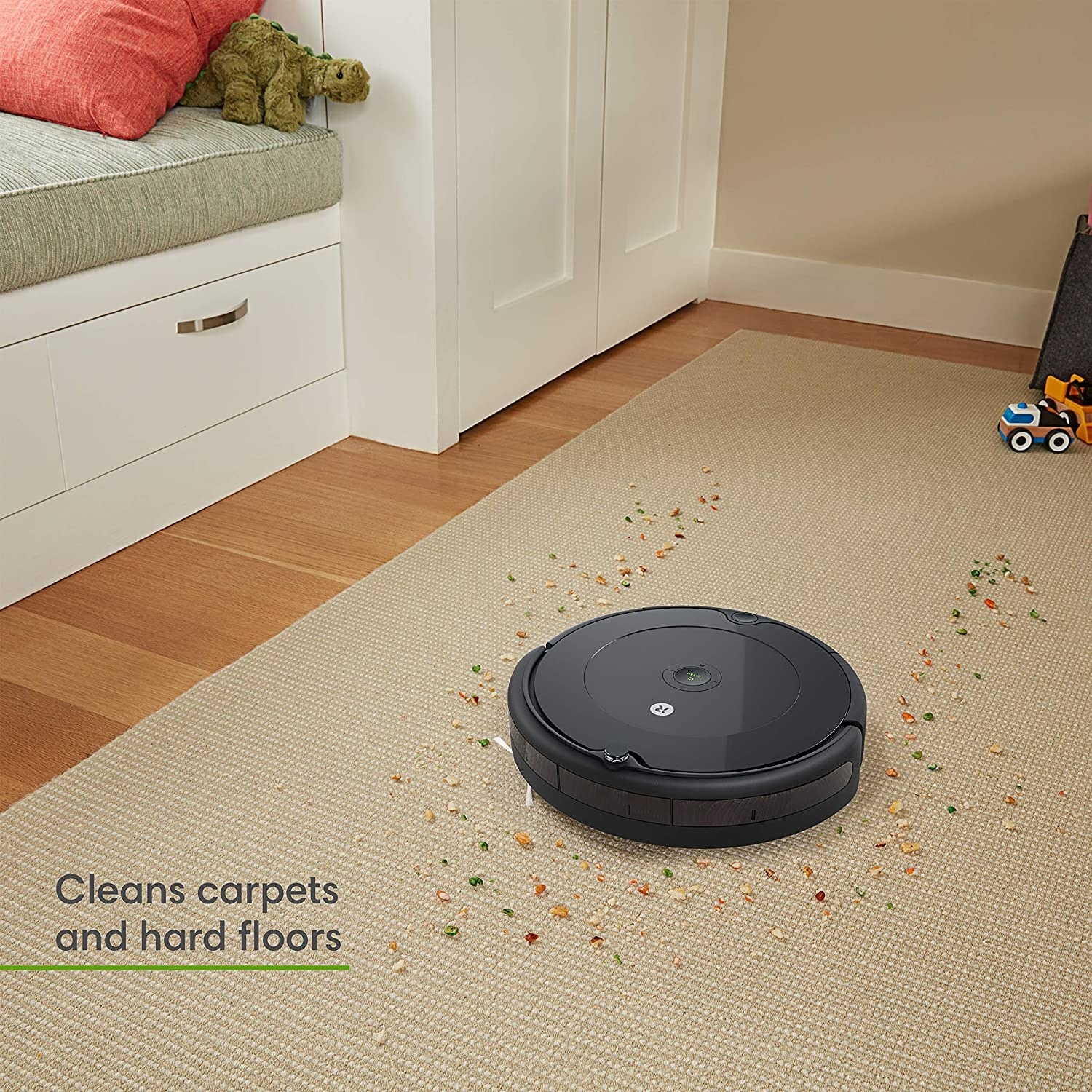 The black roomba vacuuming up a carpet, with text that it cleans carpets and hard floors