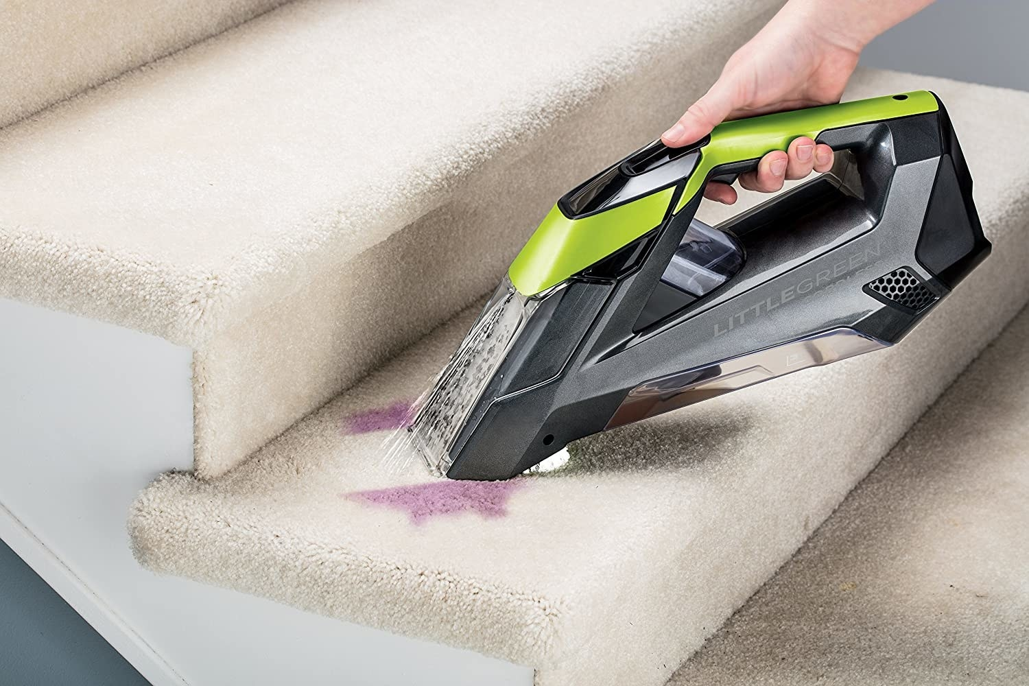A handheld vaccuum getting rid of a dark carpet stain