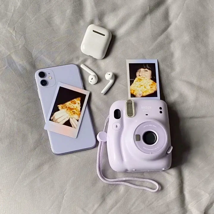 A small instant camera lying on a bed with a couple photos, a phone, and a pair of earpods nearby