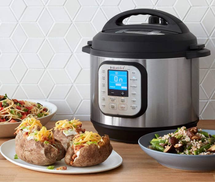 An Instant Pot on a kitchen counter beside yummy looking food