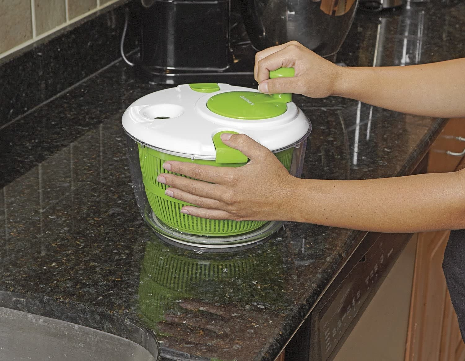 A person cranks a salad spinner on a kitchen counter