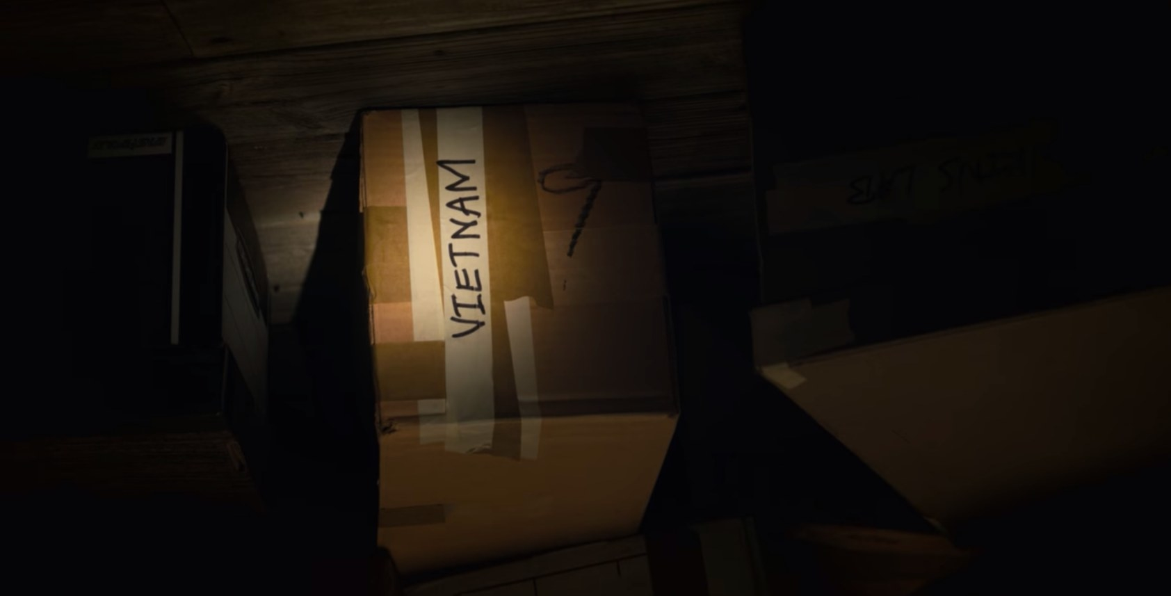 """A dark room with a flashlight hilighting a box with the word """"Vietnam"""" written on it"""