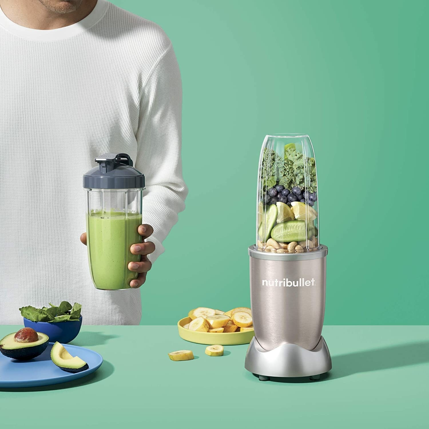 A person holding a kale smoothie next to the Nutribullet