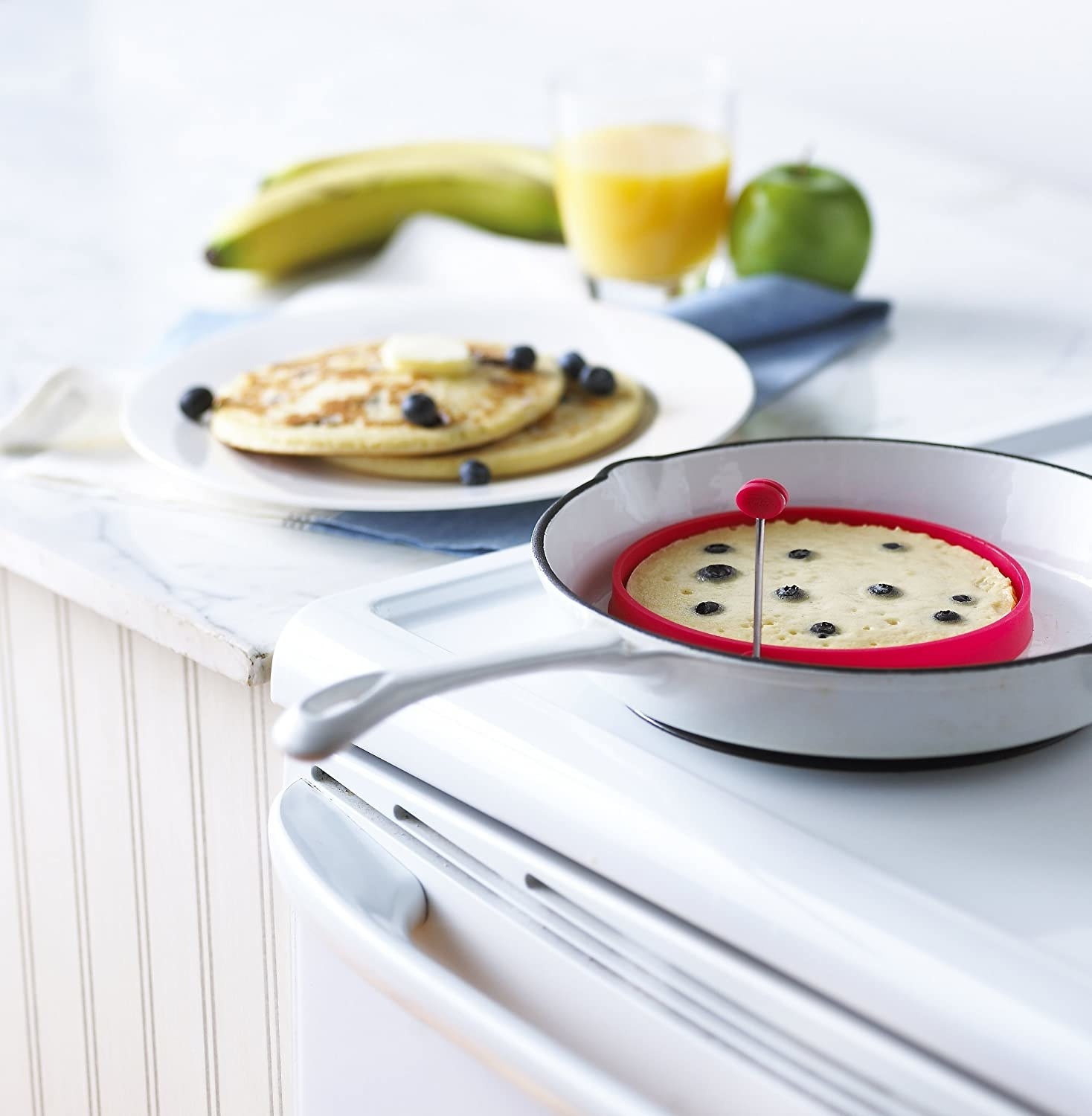 A pancake ring has batter in it in a pan on a stove