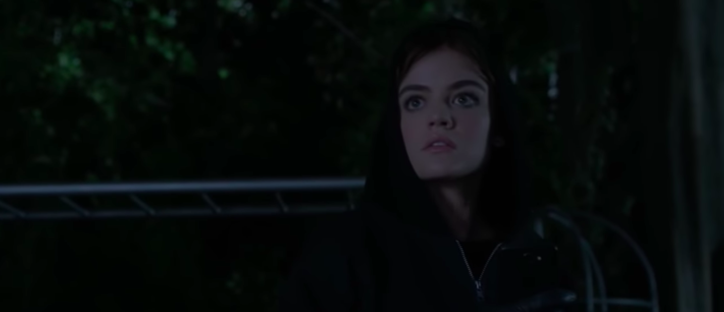 Aria wearing a black hoodie standing outside in the dark.