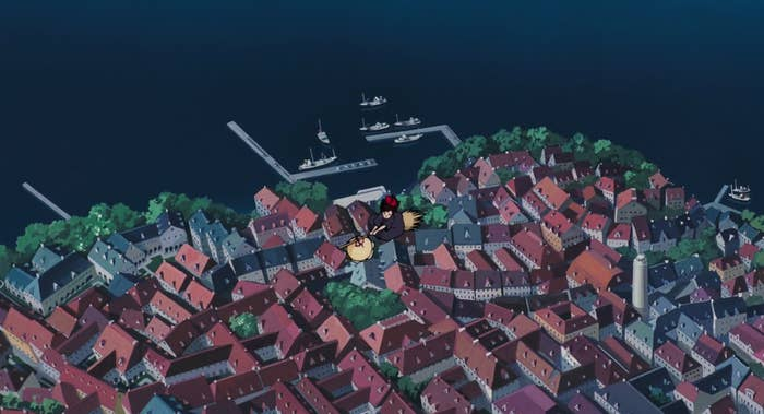 A still of an animated witch flying over a seaside town