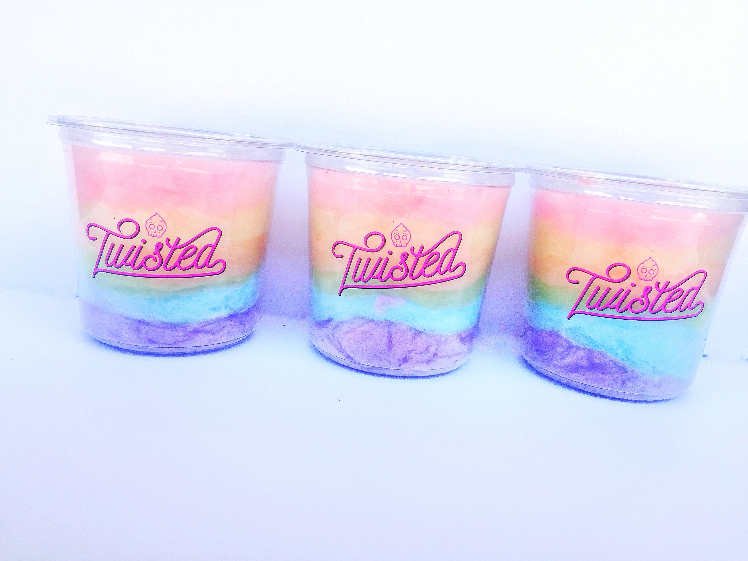 A picture of three tubs of rainbow cotton candy.