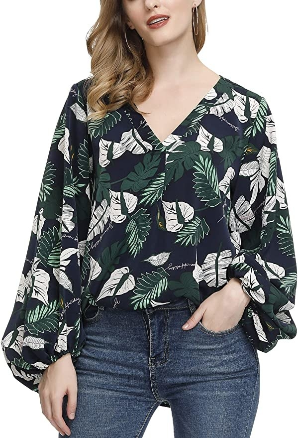 Model wearing long sleeve blouse with balloon sleeves and a dark blue and green botanical print