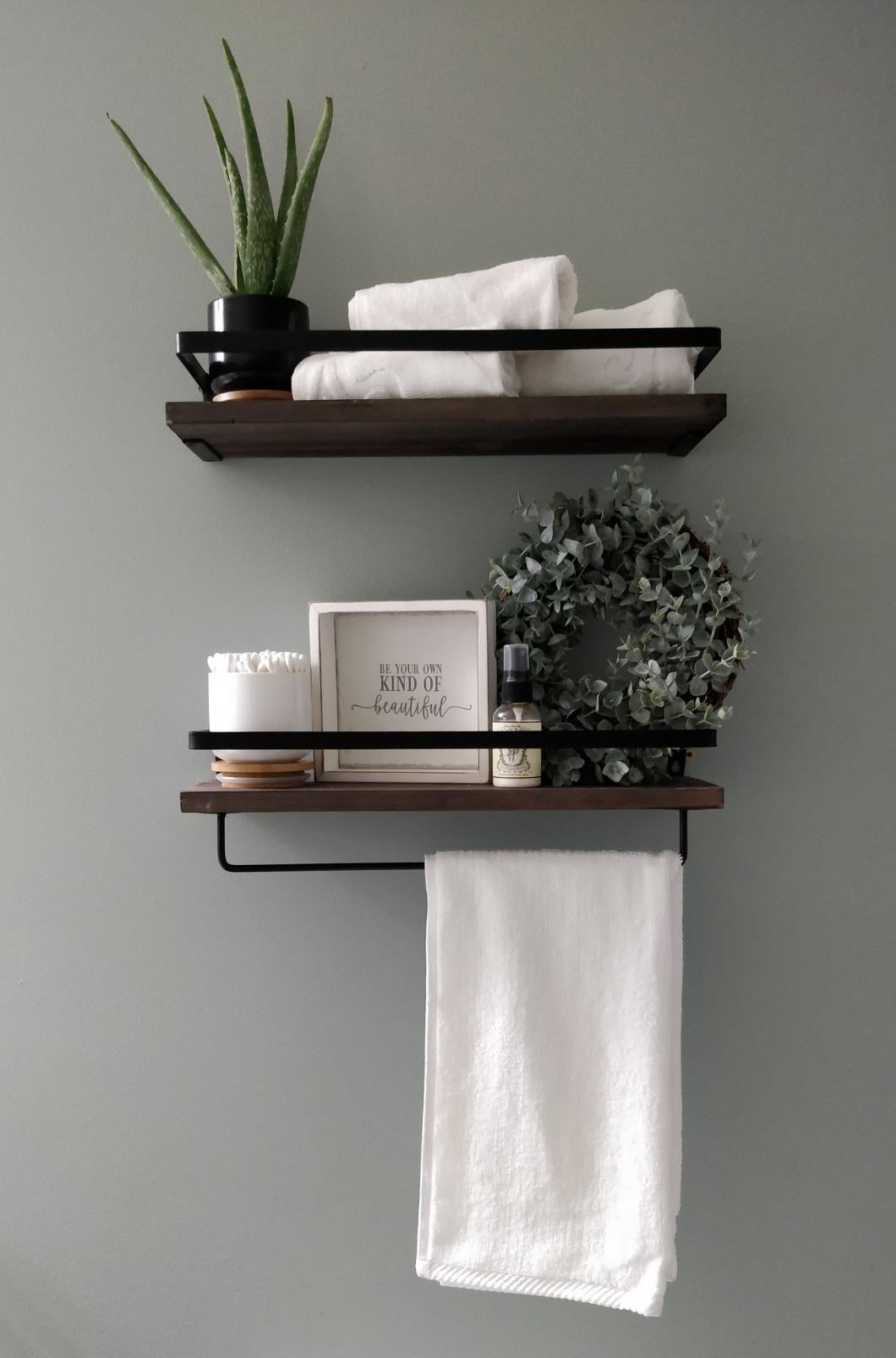 Reviewer pic of the two hanging shelves on the wall with towels and other bathroom items on them