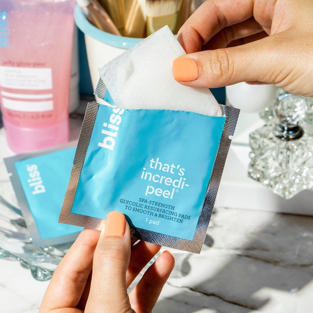 model taking white wipe out of blue packaging