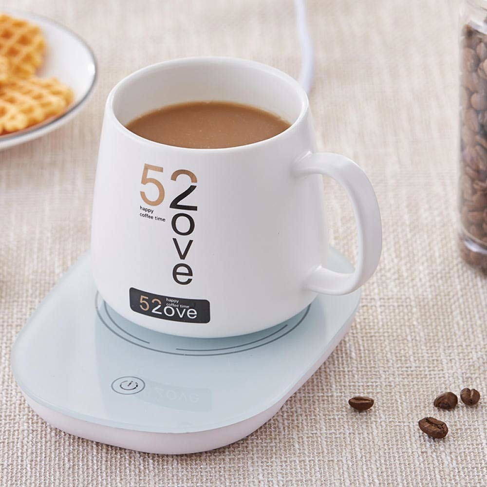 A mug of coffee being warmed on the device with coffee beans and a plate of waffles next to it.