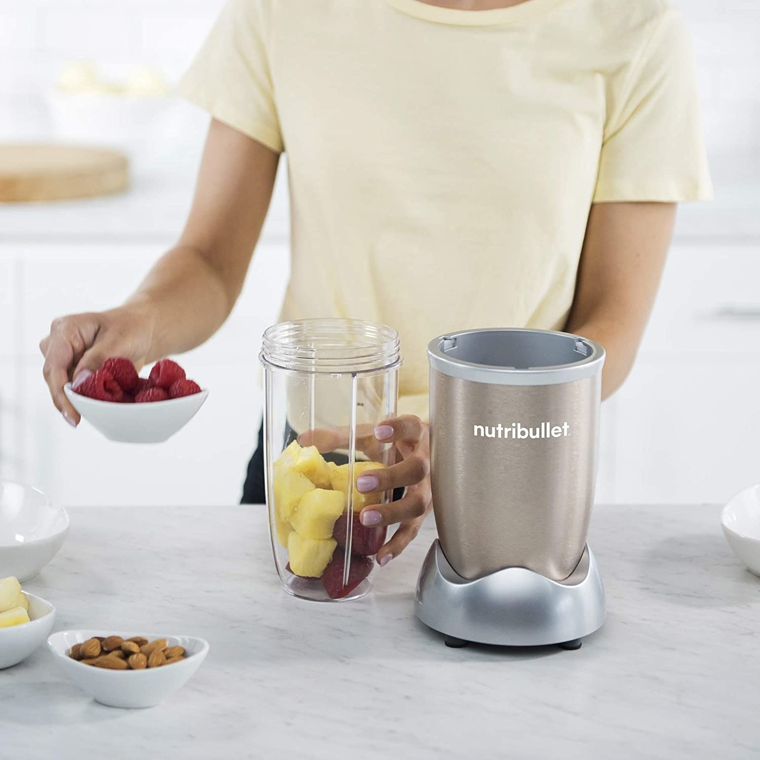 A person putting fruit into the blender cup