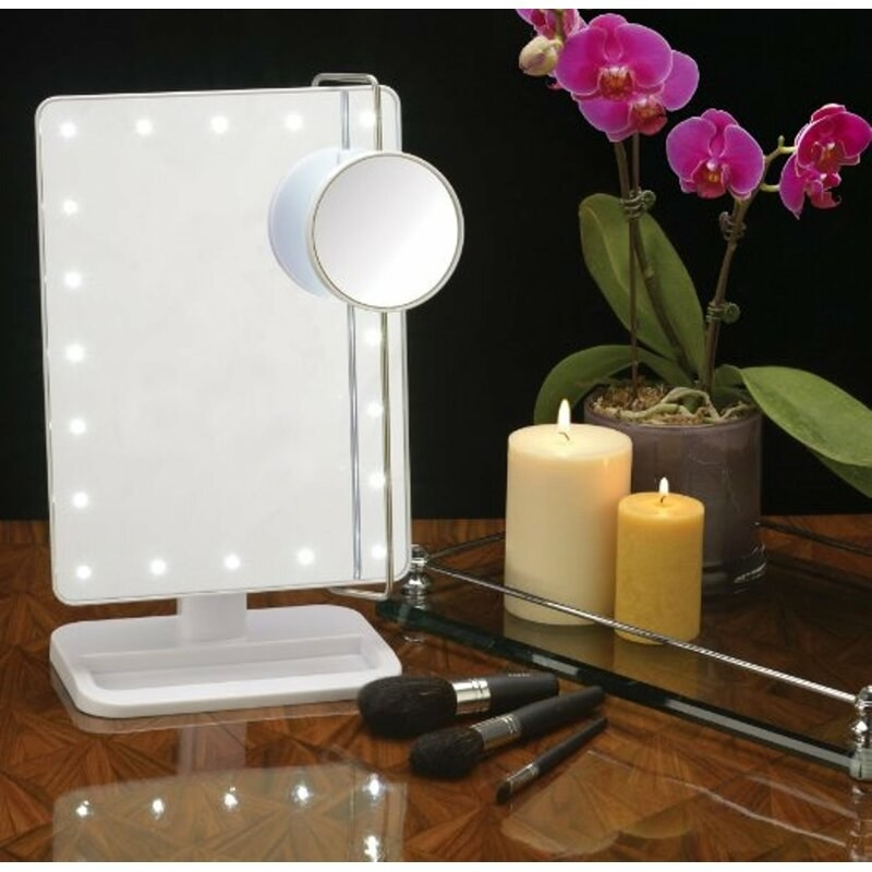 A mirror with LED lights around, candles and makeup brushes