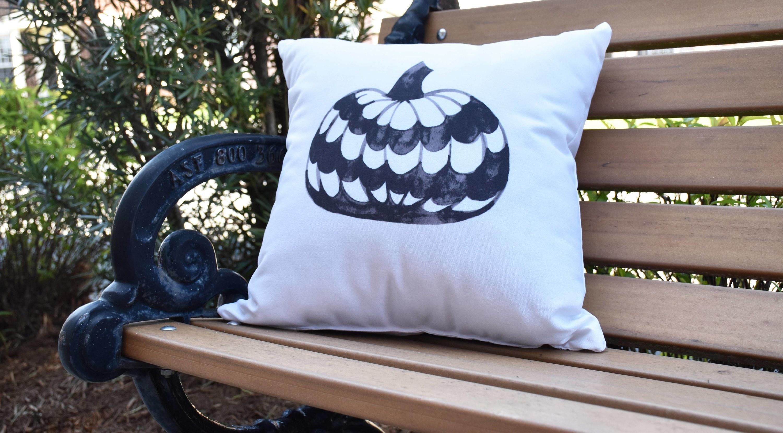 Halloween decorative pumpkin pillow on a bench