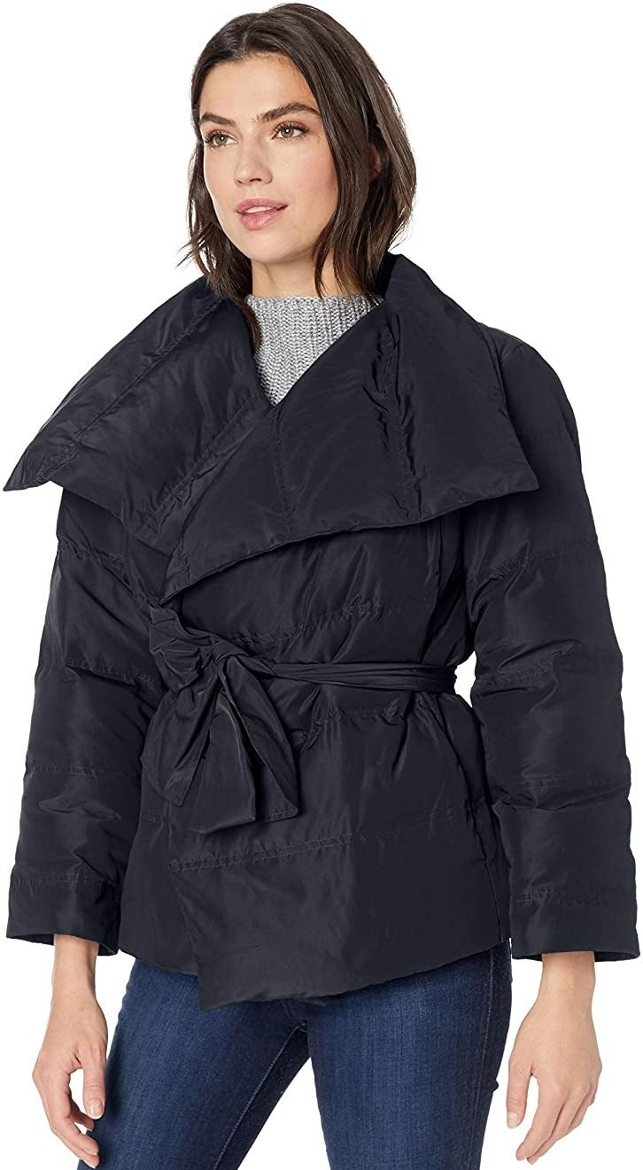 Model in black coat with a tie belt