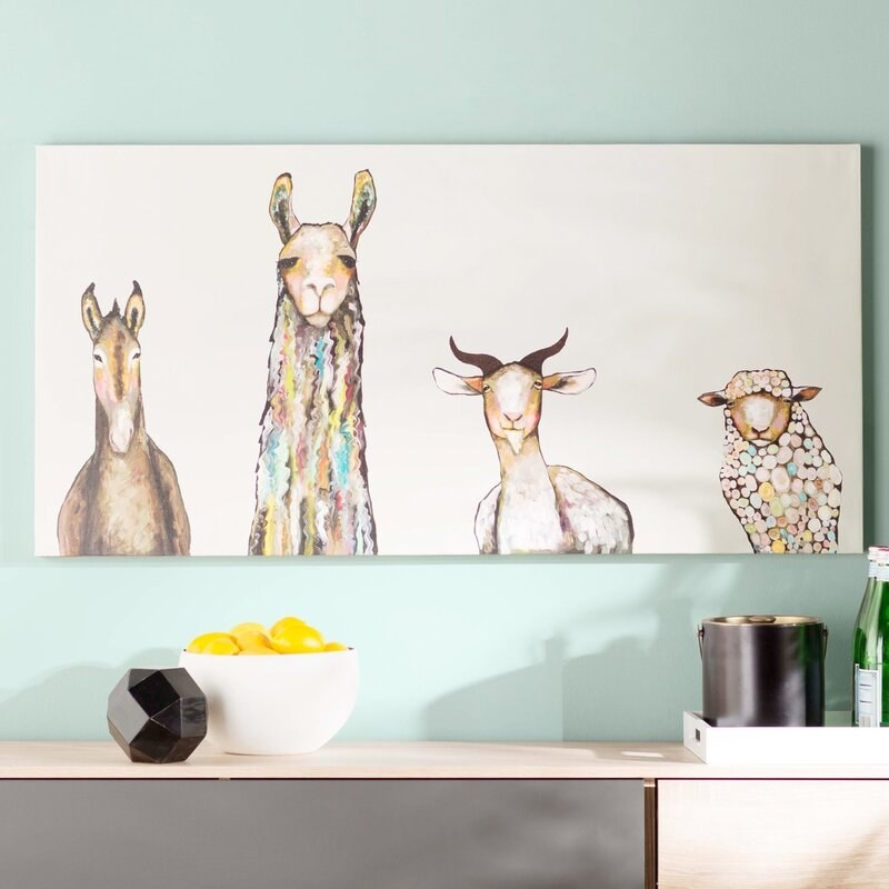 A painting with farm animals on it above a credenza