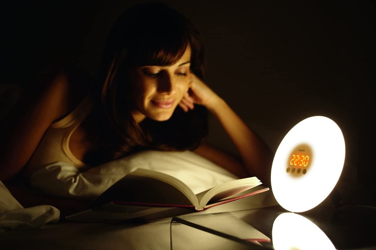A person reads by the light of the alarm clock
