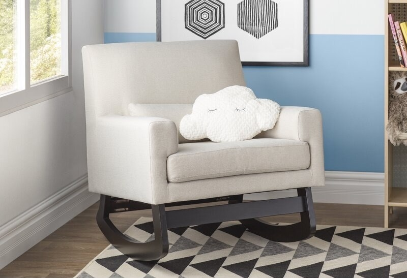 A rocking chair inside a kid's room with a pillow shaped like a cloud on it