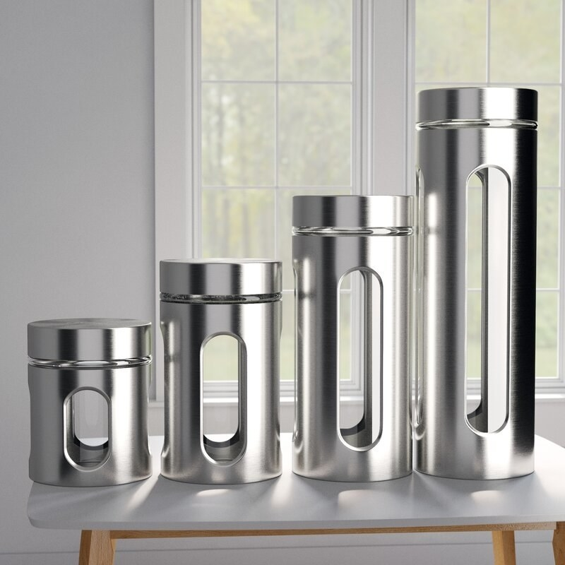 Four stainless steel kitchen canisters with clear glass windows