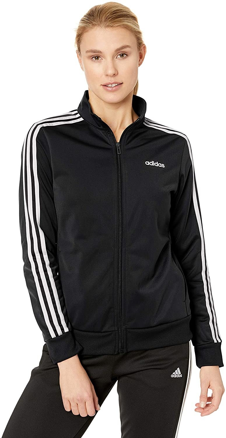 Model in the black zip-front jacket with adidas logo on front corner and white stripes down the sleeves