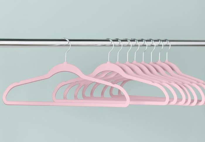 the pink hangers hanging on a metal rod
