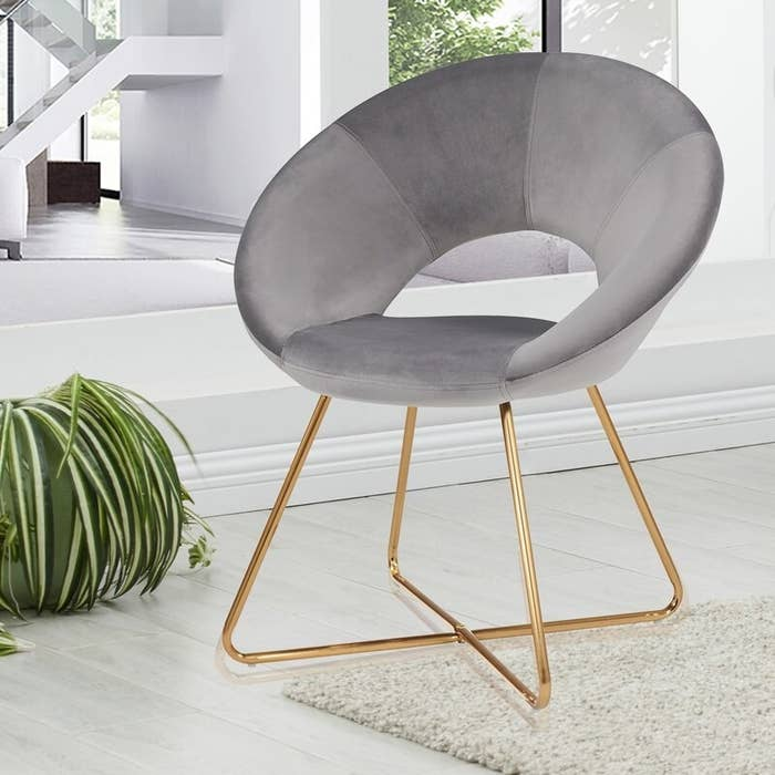 A gray chair with gold base legs