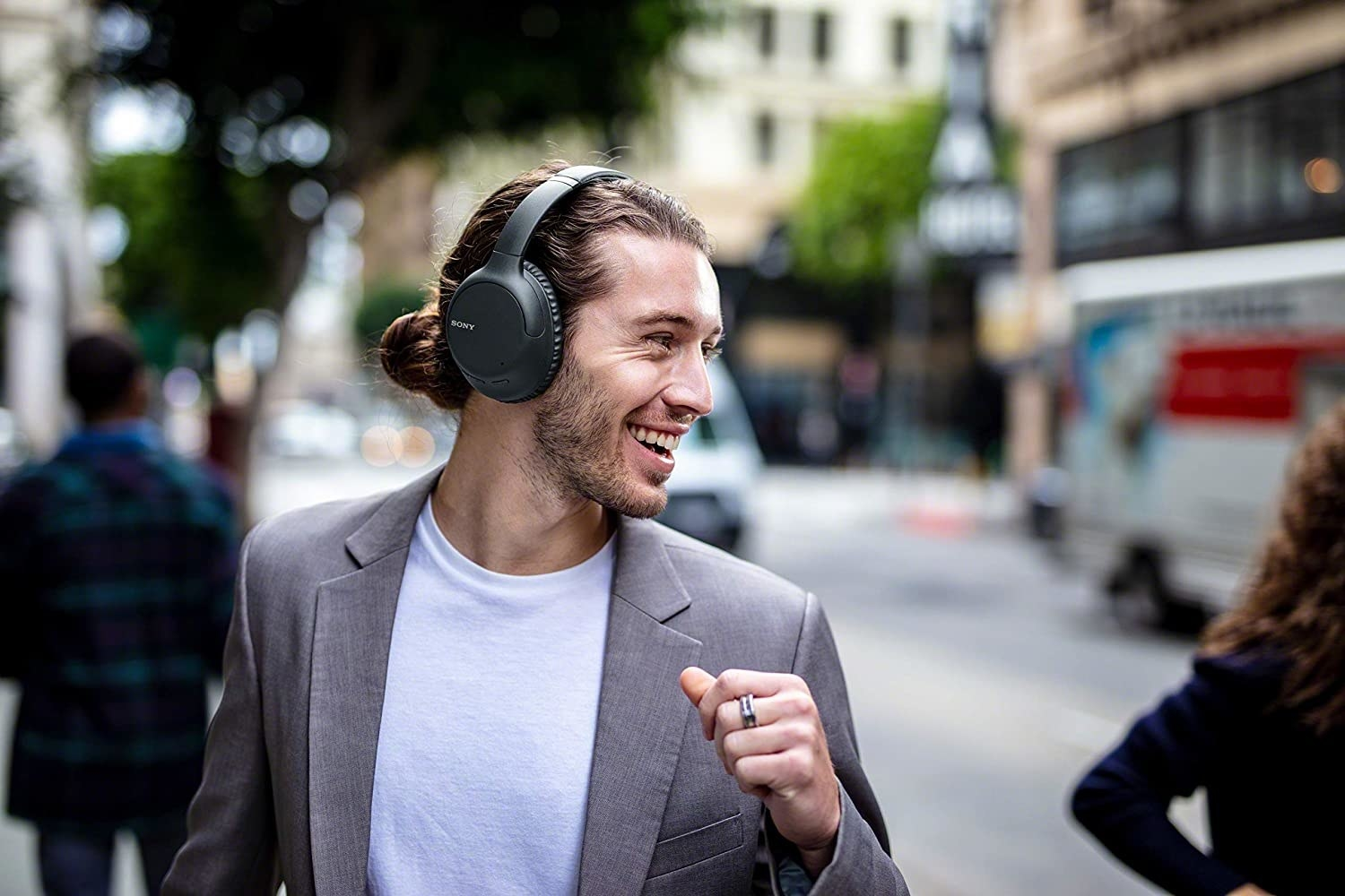 A person walking down the street with a pair of over-ear headphones on
