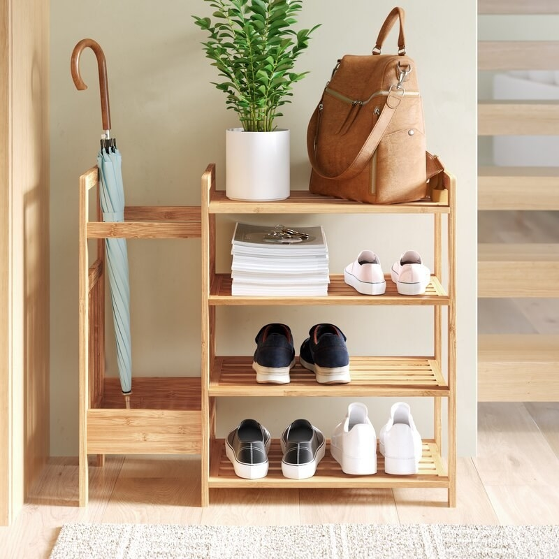 Wooden entryway shelving holding shoes, magazines, a plant, a bag and an umbrella